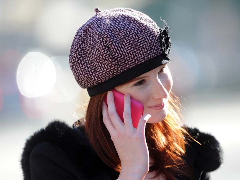 """A young woman uses an iPhone mobile phone in Melbourne, Wednesday, June 1, 2011. A report released overnight by the World Health Organisation's cancer research wing said radio waves emitted by mobile phones are """"possibly carcinogenic to humans"""". (AAP Image/Julian Smith) NO ARCHIVING"""