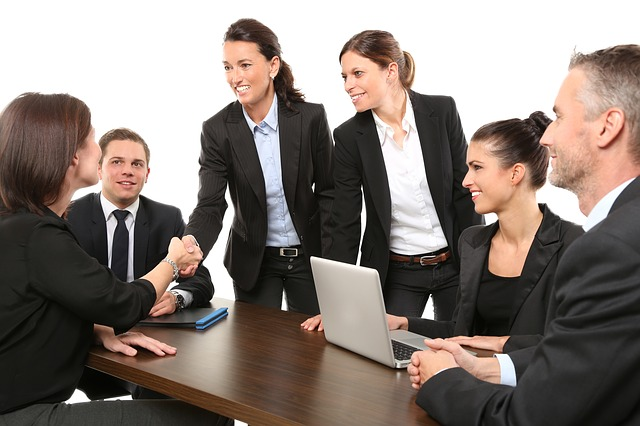 Happy business people shaking hands perfect for follow-up NPS